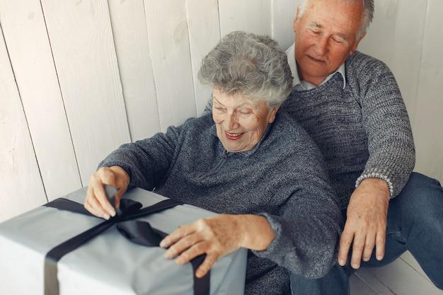 Elegante pareja de ancianos sentados en casa con regalos de navidad Foto gratis