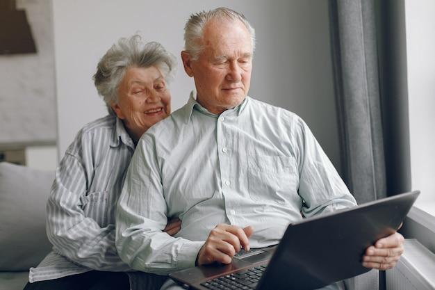 Elegante pareja de ancianos sentados en casa y usando una computadora portátil Foto gratis