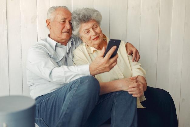 Elegante pareja de ancianos sentados en casa y usando un teléfono Foto gratis