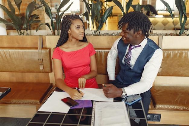 Elegante pareja negra sentada en un café y conversación de negocios Foto gratis