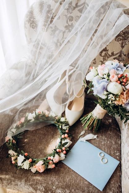 Elegante ramo de novia con cinta, invitaciones de boda, anillos de compromiso y zapatos para la novia. Foto Premium