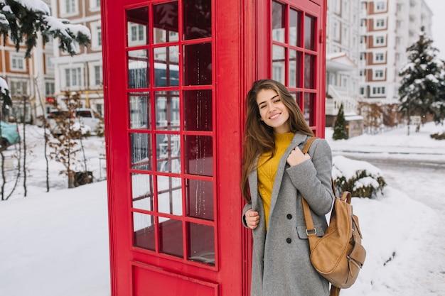 Elegante retrato británico de encantadora joven con cabello largo morena caminando en la calle cerca de la cabina de teléfono roja en la calle llena de nieve. tiempo de nieve fría, sonriendo, vacaciones de invierno, alegría. Foto gratis