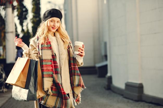 Elegante rubia linda caminando en una ciudad Foto gratis