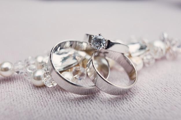 097f984d6b77 Elegantes anillos de boda de plata hechos de oro blanco se encuentran en la  pulsera de cristal.