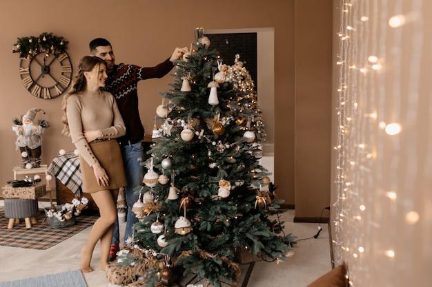 Elegantes hombres y mujeres vestidos con bata plateada se abrazan tiernamente de pie ante un árbol de navidad Foto gratis