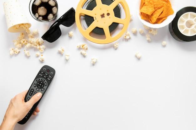 Elementos de la película sobre fondo blanco y persona con un control remoto de tv Foto gratis