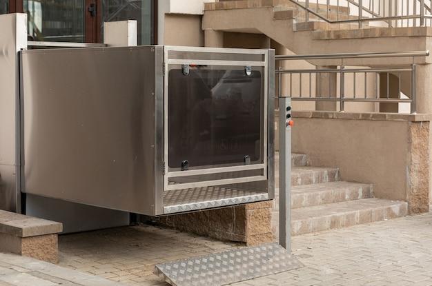 Elevador de escaleras, elevador de plataforma, elevador de personas discapacitadas cerca de las modernas instalaciones de apartamentos, vista diagonal Foto Premium