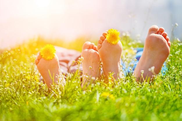 Embroma pies con las flores del diente de león que mienten en hierba verde en día soleado. concepto feliz del chidlhood. Foto Premium