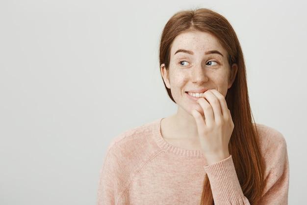 Emocionada mujer pelirroja sonriente toca el labio y mira a la izquierda con tentación Foto gratis