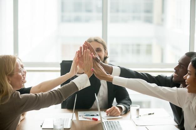Emocionado equipo de negocios multirracial feliz que da alta-cinco en la reunión de la oficina Foto gratis