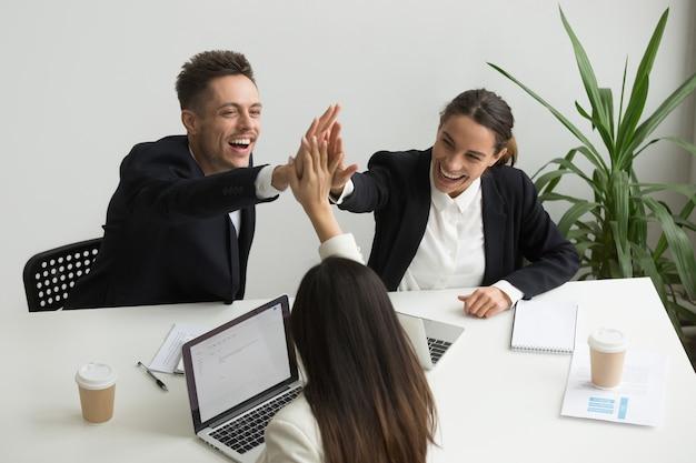 Emocionado equipo de la oficina del milenio que da alta cinco juntos, concepto de trabajo en equipo Foto gratis