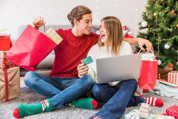 Emocionado hombre y mujer con compras y portátil Foto gratis