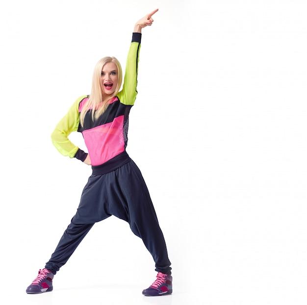 Emocionado joven activo femenino posando con su brazo en el aire vistiendo traje deportivo copyspace aislado Foto gratis