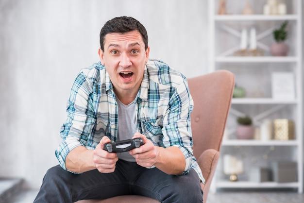 Emocionado joven varón sentado en el sillón y jugando con gamepad Foto gratis