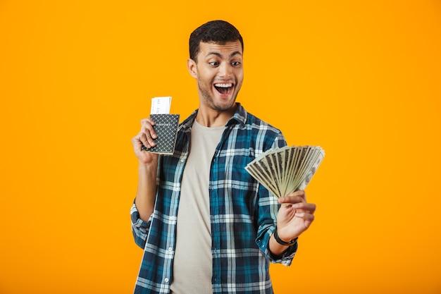 Emocionado joven vestido con camisa a cuadros que se encuentran aisladas sobre fondo naranja, mostrando billetes de dinero, sosteniendo el pasaporte con boletos de avión Foto Premium