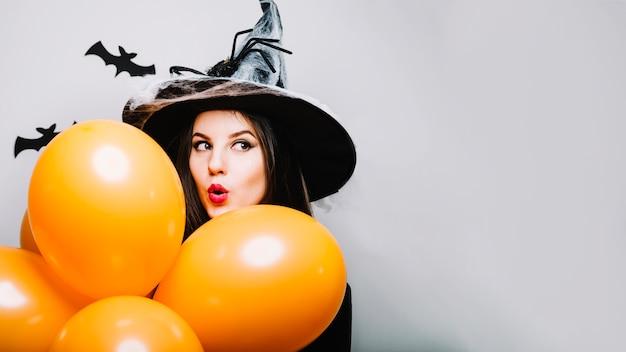 Emocionado niña bruja con globos Foto gratis