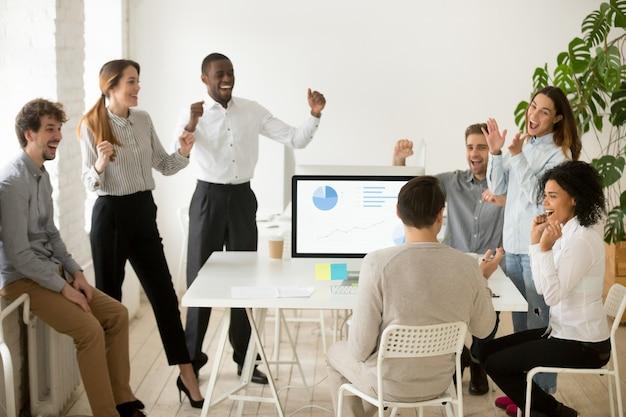 Emocionados por las buenas noticias, colegas motivados que celebran juntos el éxito corporativo. Foto gratis