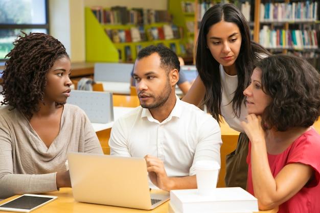 Emocionados colegas discutiendo algunas preguntas en la biblioteca Foto gratis