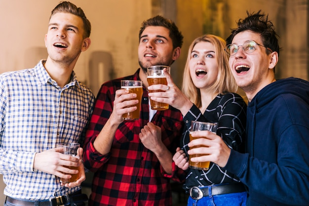 Emocionados jóvenes amigos disfrutando de la cerveza mientras miran algo. Foto gratis