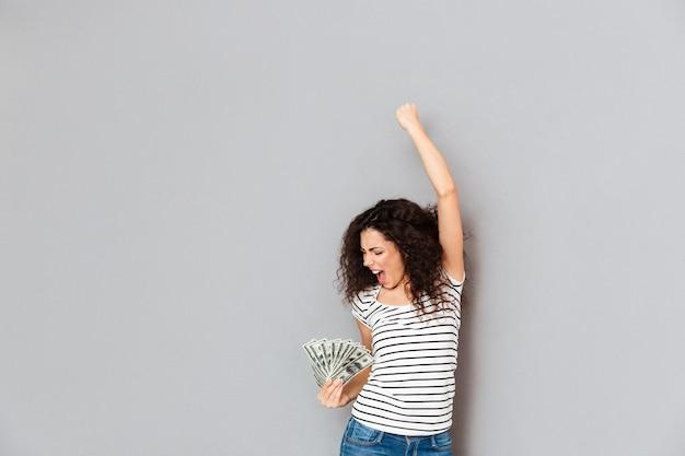 Emocional mujer en camiseta a rayas actuando como ganador sosteniendo fan de billetes de 100 dólares y apretando el puño en el aire sobre la pared gris Foto gratis