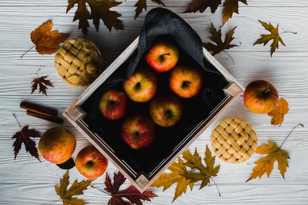 Empanadas y hojas cerca de las manzanas Foto gratis
