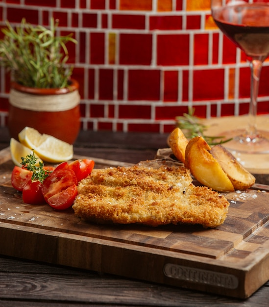 Empanadas de pollo fritas servidas con papas fritas, limón y tomate sobre tabla de madera Foto gratis