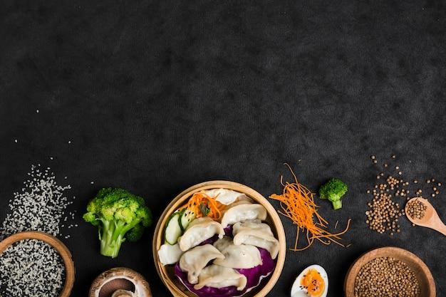 Empanadillas cocidas dentro del vapor de bambú con huevos; brócoli; semillas de sésamo y cilantro sobre fondo negro de textura Foto gratis