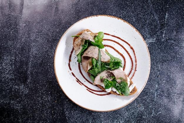 Emparedado de pan con carne de pavo, mozarella y hierbas, en plato blanco. Foto gratis