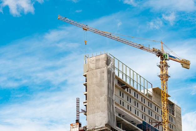 Emplazamiento de la obra con grúa y edificio. sector inmobiliario. el equipo de grúa utiliza el equipo de elevación del carrete en el sitio de construcción. edificio de acero y hormigón. grúa de trabajo contra el cielo azul y la nube blanca Foto Premium