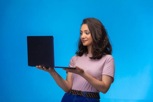 Empleada con un portátil negro con videollamada y sonriendo. Foto gratis