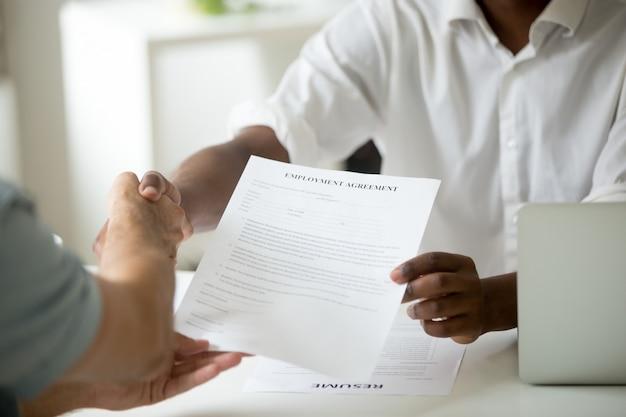 Empleado afroamericano que sostiene un acuerdo de empleo candidato a apretón de manos, vista de cerca Foto gratis