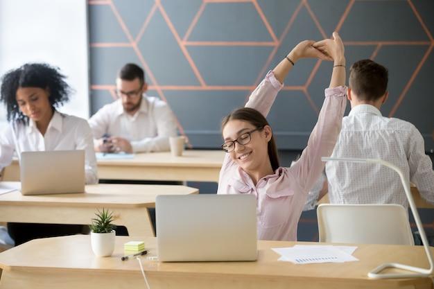 Empleado del milenio que se extiende tomando un descanso del trabajo de la computadora para relajarse Foto gratis