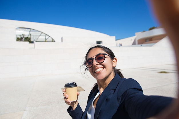 Empleado de oficina alegre tomando café para llevar Foto gratis
