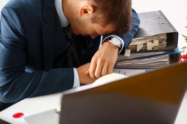 Empleado de oficina cansado en traje de tomar una siesta en la mesa de trabajo llena de exámenes. sleepy white collar frustración profesional freelance empleo falla estudio problema baja energía baja Foto Premium