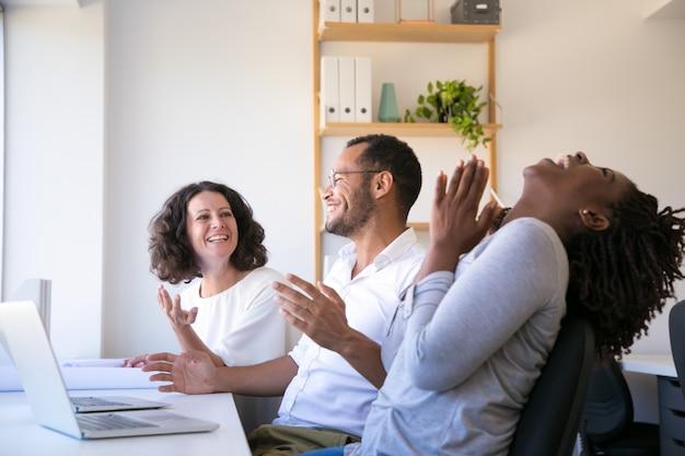 Empleados alegres hablando y riendo en el lugar de trabajo Foto gratis