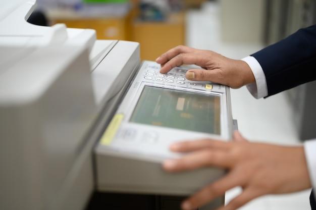 Los empleados están copiando documentos con una fotocopiadora en la oficina. Foto Premium