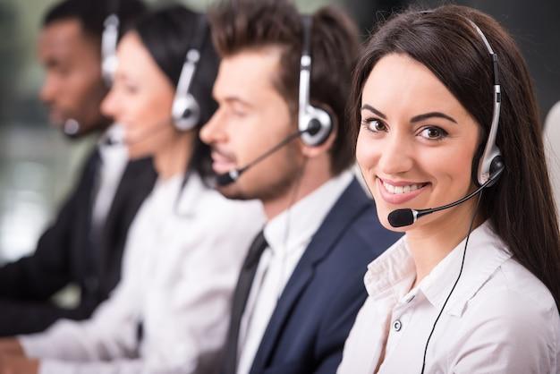 Los empleados están sonriendo y trabajando en computadoras. Foto Premium