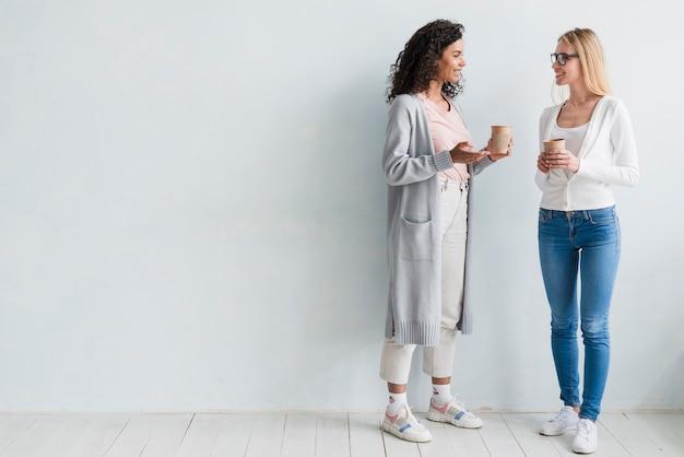 Empleados multirraciales de pie y sosteniendo tazas sobre fondo blanco Foto gratis