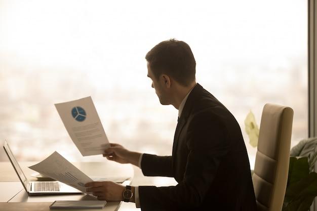 Emprendedor analizando documentos de estadísticas de negocios. Foto gratis