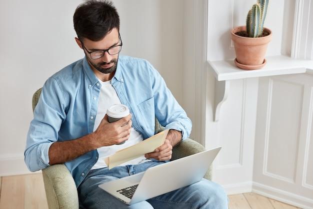El emprendedor serio se ocupa de los negocios, trabaja en casa, se concentra en los documentos, tiene una computadora portátil sobre las rodillas, sostiene el café para llevar, se sienta en un cómodo sillón. Foto gratis