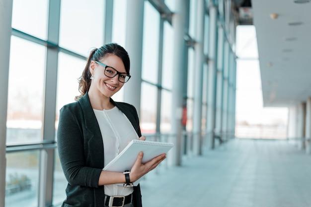 Empresaria acertada y satisfecha, sosteniendo un cuaderno, mirando la cámara. Foto Premium