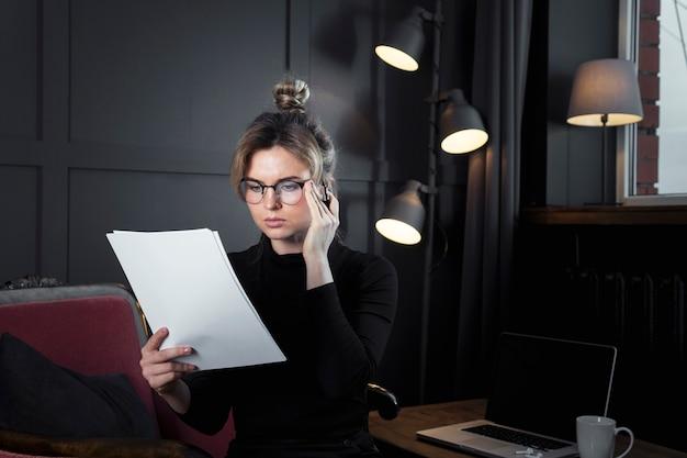 Empresaria adulta que mira en los papeles Foto gratis