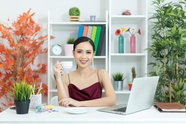 La empresaria asiática toma un descanso para tomar café después de trabajar en la computadora de computadora portátil en el escritorio Foto gratis