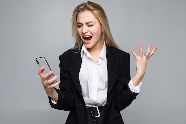 Empresaria bonita sorprendida que charla por el teléfono que se coloca aislado. Foto gratis