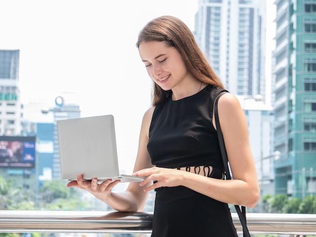 Empresaria caucásica usando una computadora portátil y sonriendo mientras está de pie en la oficina moderna en el centro de la ciudad Foto Premium