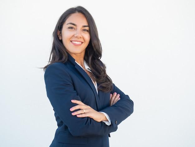 Empresaria confiada sonriente que presenta con los brazos cruzados Foto gratis