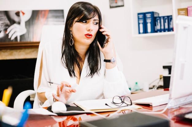 Empresaria de moda en la oficina hablando por tel fono for La oficina telefono