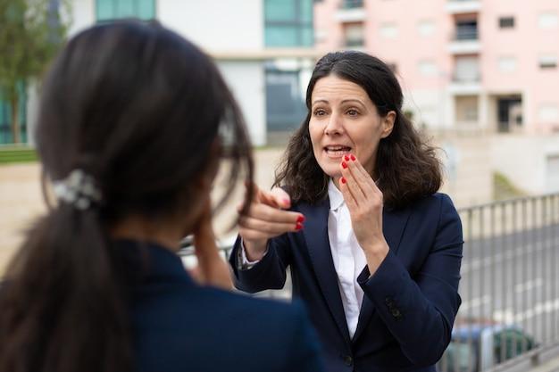 Empresaria emocional hablando con colega Foto gratis