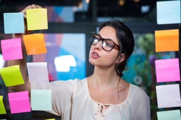 Empresaria escribiendo en nota adhesiva Foto Premium