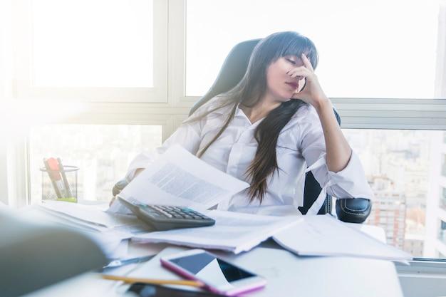 Empresaria con el escritorio desordenado que duerme en la oficina Foto gratis